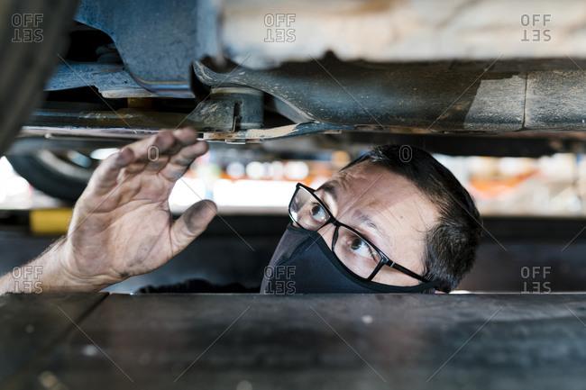 Close-up of male mechanic wearing mask examining car in garage