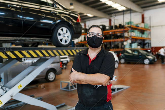 Male mechanic wearing mask with arms crossed standing in workshop