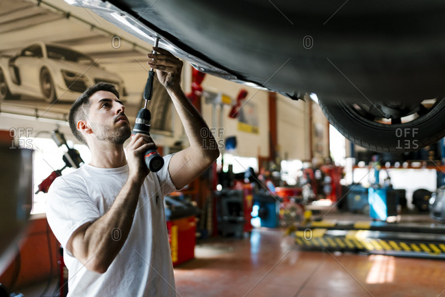 Young mechanic repairing car with work tool in auto repair shop