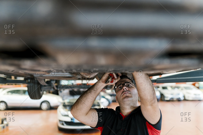 Mid adult man examining car in auto repair shop