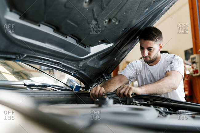 Young man repairing car while standing in auto repair shop