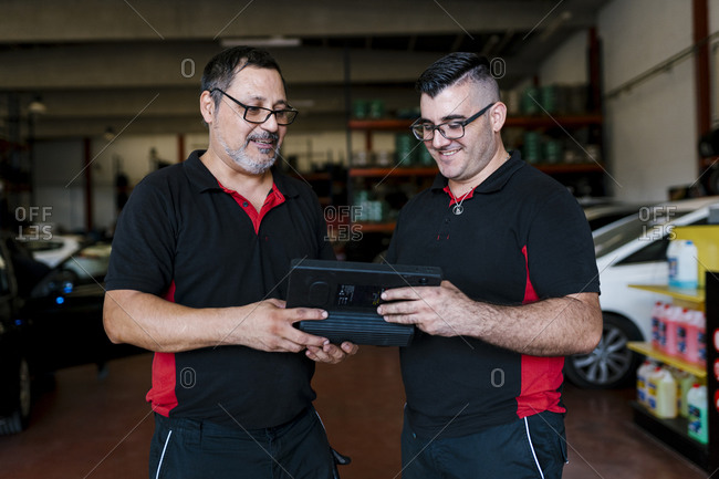 Colleagues discussing over digital tablet while standing in auto repair shop