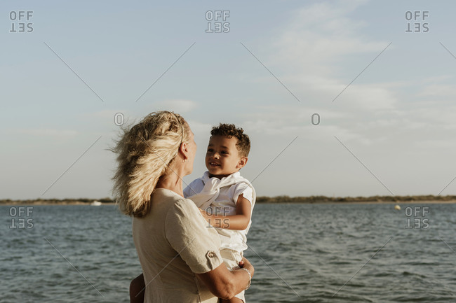 Grandmother picking up grandson in arms while standing at beach