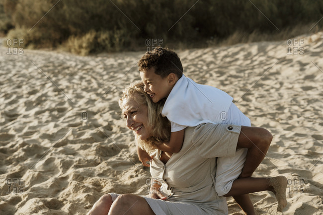 Grandson embracing grandmother from back while sitting on sand at beach