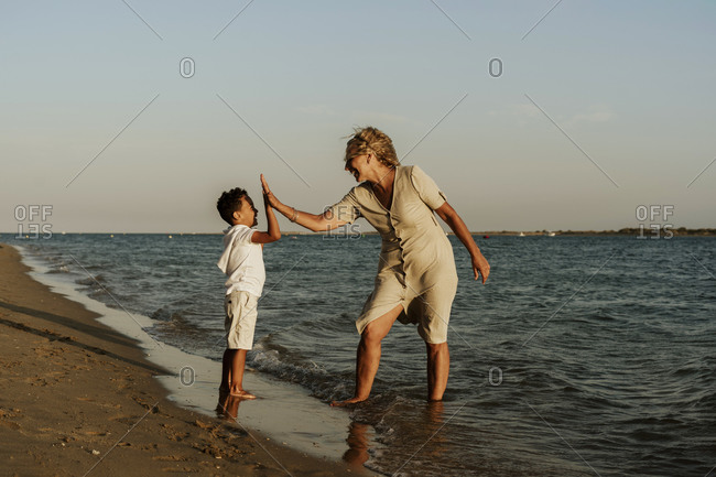 Happy grandmother and grandson doing high five to each other at beach during sunset