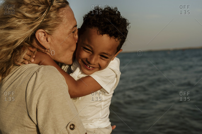 Grandmother kissing grandson while carrying him at beach during sunset