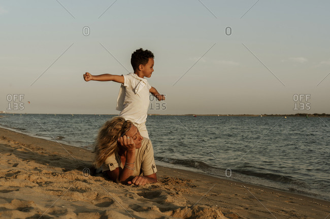 Grandmother lying on sand while grandson standing on her back with arms outstretched at beach during sunset