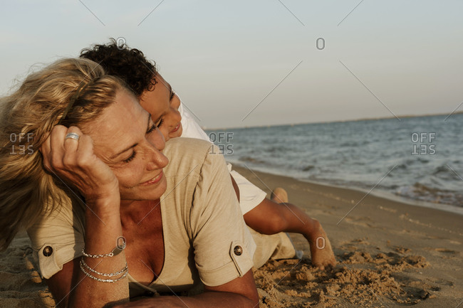 Grandmother lying on sand while grandson sleeping on her back at beach during sunset