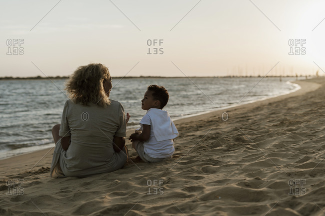 Grandmother and grandson talking with each other at beach during sunset