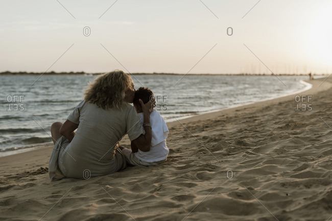 Grandmother kissing grandson while spending leisure time at beach during sunset