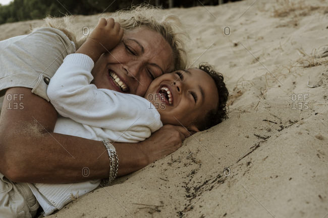 Grandmother and grandson embracing each other while lying down on sand at beach during sunset