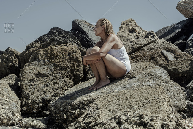 Senior woman wearing swimwear sitting on rock against clear sky during sunny day
