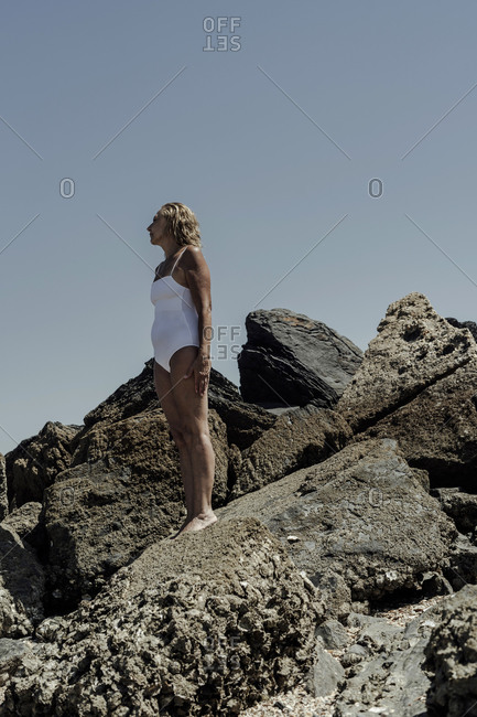 Senior woman wearing swimwear standing on rock against clear blue sky during sunny day