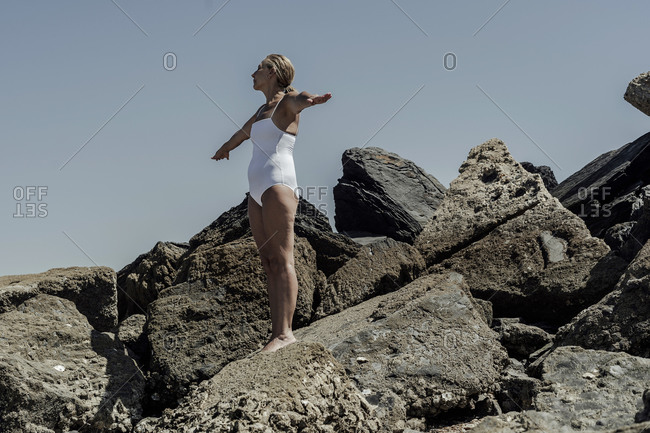 Senior woman in swimwear with arms outstretched standing on rock at beach