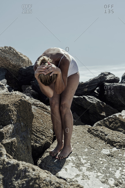 Senior woman wearing swimwear with head in hands standing on rocky beach against clear sky