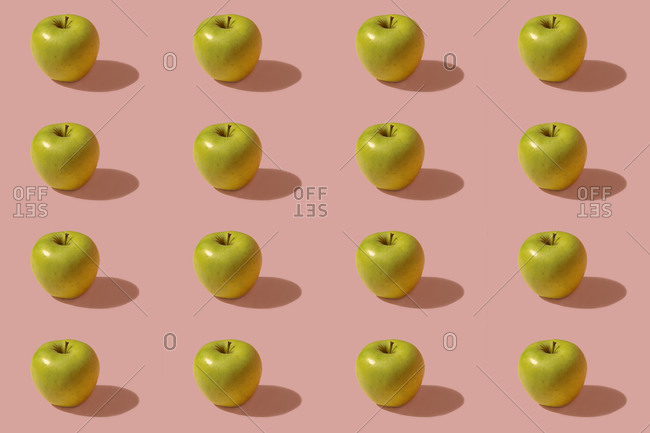 Pattern of green apples against pink background