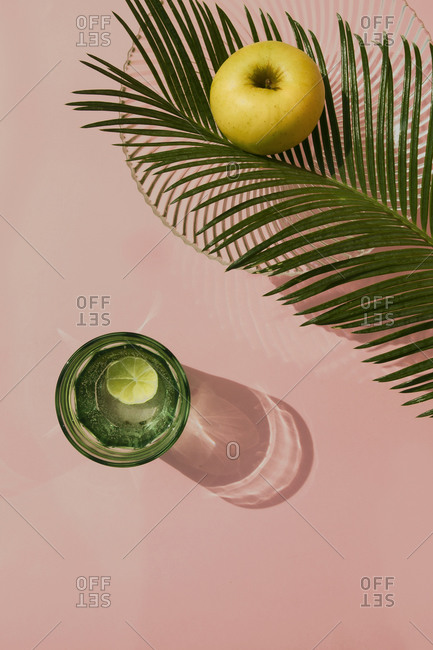 Studio shot of palm leaves- glass bowl- glass of carbonated water and single apple