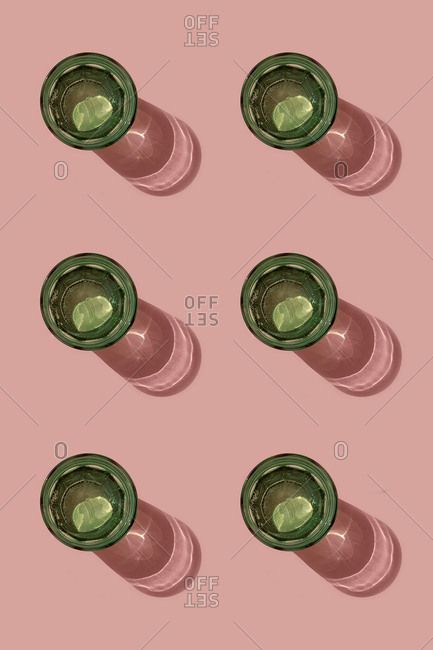 Pattern of green glasses of carbonated water