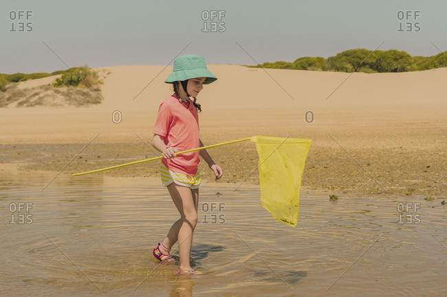 Girl with fishing net walking in sea against clear sky during sunny day