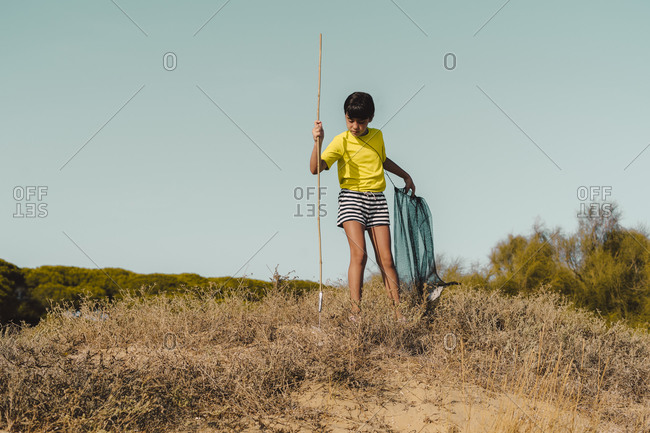 Girl looking down while collecting garbage at beach