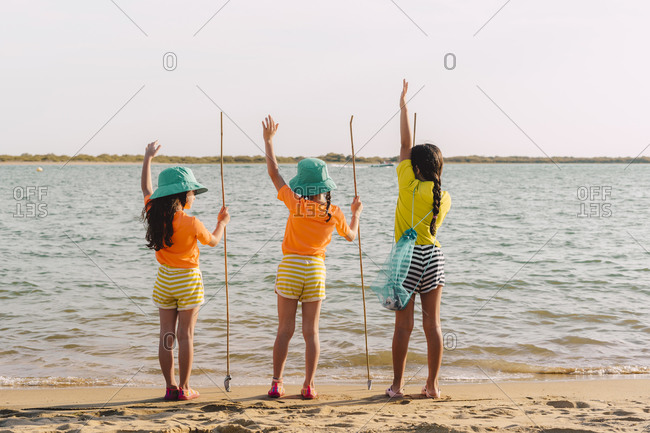 Friends looking at view with hand raised standing on beach