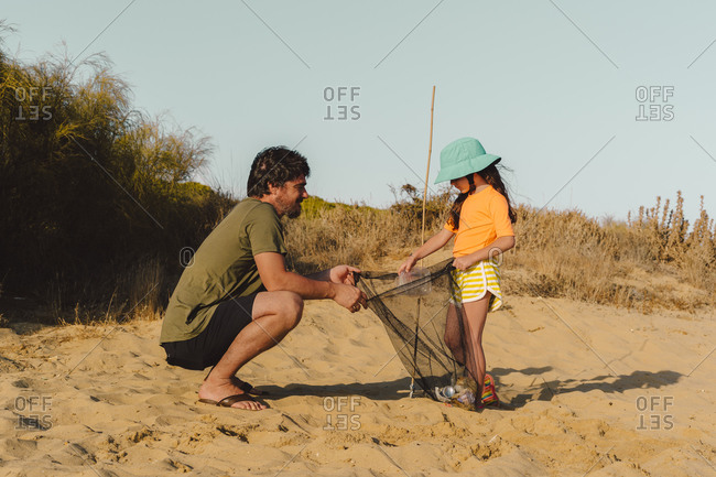 Mature man and little girl picking up garbage at beach