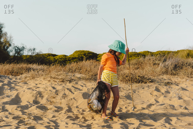 Girl carrying garbage while standing on stand at beach