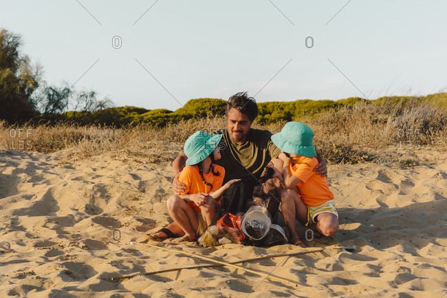 Sisters cleaning garbage with father at beach