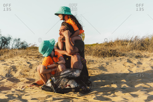 Father and daughters sitting on sand with garbage bag during sunny day