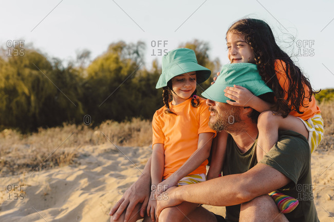 Daughters siting on shoulder and lap of father at beach