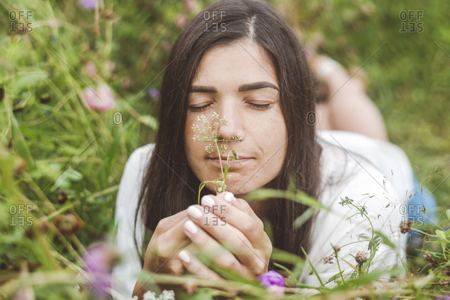 Close-up of mid adult woman with eyes closed smelling flowers while lying on land