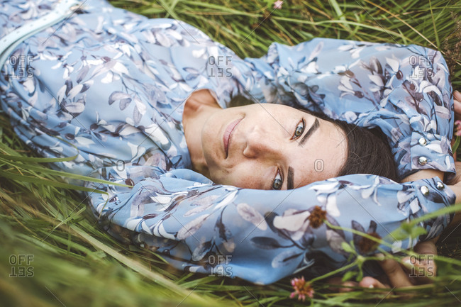 Close-up of woman with arms raised lying on plants