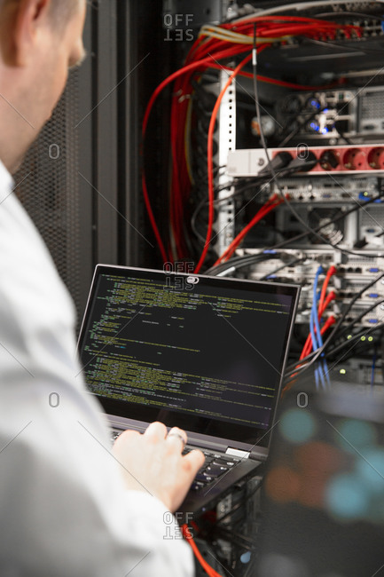Close-up of male IT professional using laptop in data center