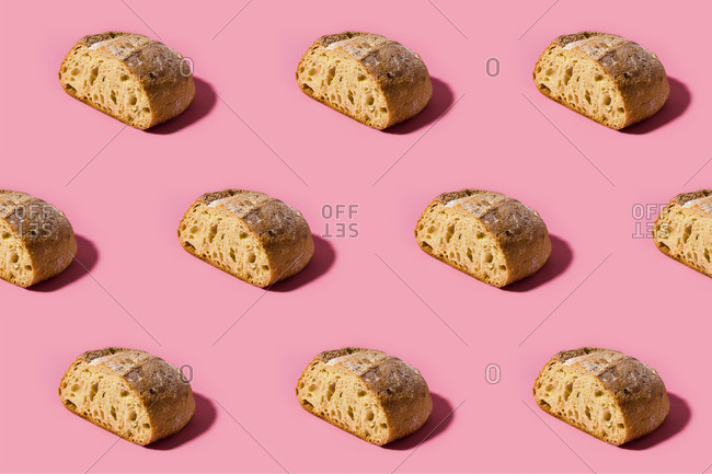 Pattern of fresh loaves of bread against pink background