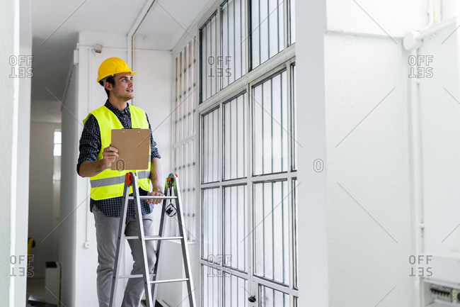 Man wearing work helmet and jacket standing on ladder by window at construction site