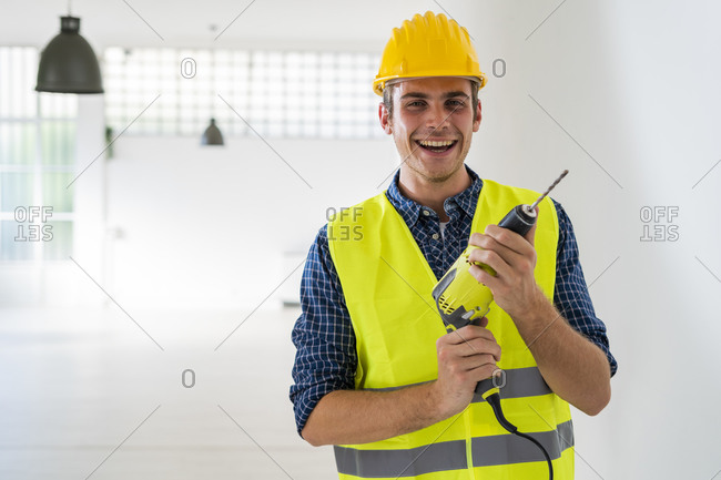 Smiling man holding drill machine while standing at office under construction
