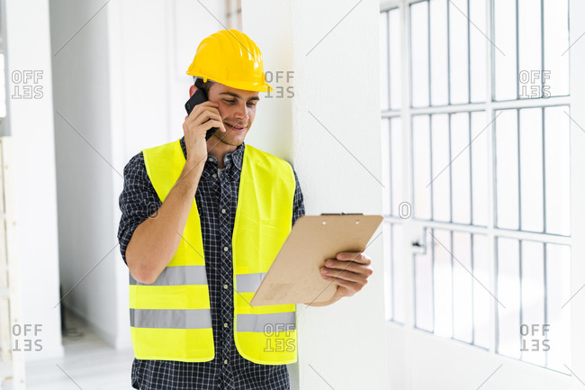 Smiling architect holding notepad while talking on mobile phone at office under construction