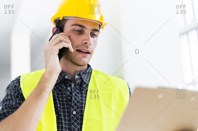Architect holding notepad while talking on mobile phone at construction site
