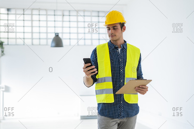 Young man wearing in work helmet and jacket using mobile phone while standing at construction site