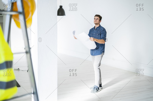 Architect holding blue print while standing at construction site