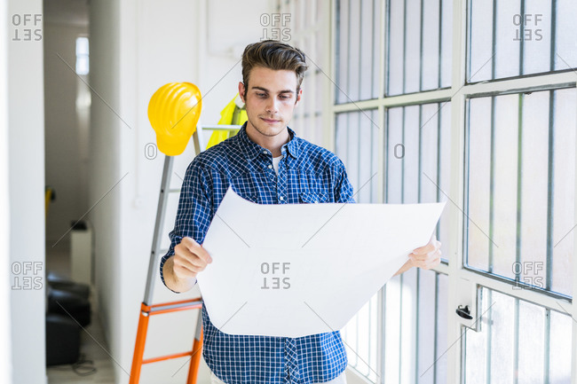 Man holding blueprint while standing by window at office under construction