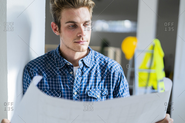 Young man examining blueprint while leaning on wall at construction site