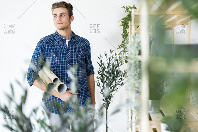 Architect holding cardboard tube while standing by potted plant rack at office