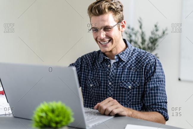 Smiling man using laptop while sitting at office
