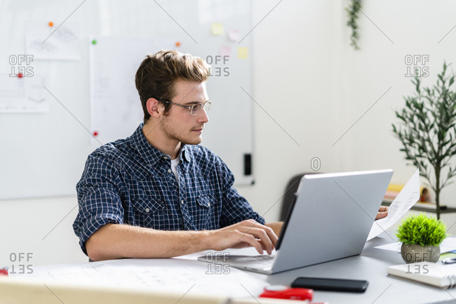 Architect working on laptop while sitting by table at office