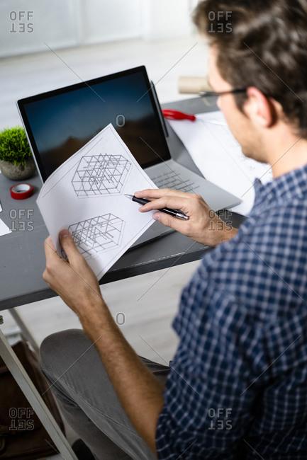 Architect analyzing blueprint while sitting at office