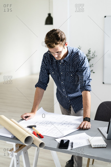 Architect analyzing blueprint while standing by desk at office