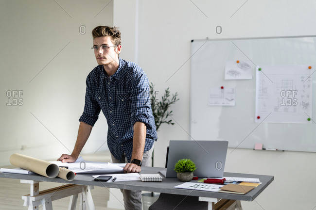 Man looking away while standing by desk at office