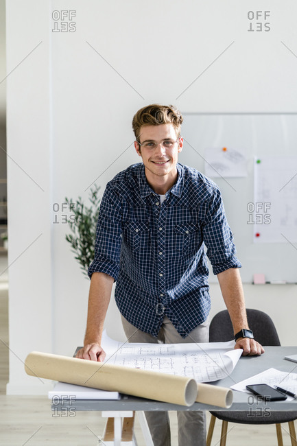 Smiling architect leaning on desk while standing at office