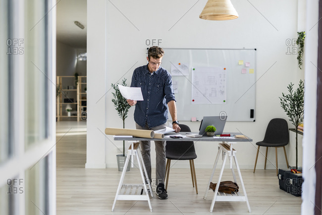 Young man standing while working at office